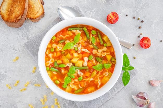 Minestrone-suppe mit frischem gemüse und nudeln in einer schüssel auf grauem betonhintergrund veganes gericht c