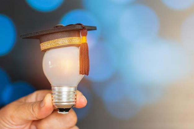 Mini abgestufter hut mit glühlampe auf händen im hellen hintergrund