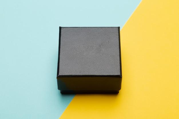 Mini-black-box-produktverpackung isoliert auf gelbem halbblau