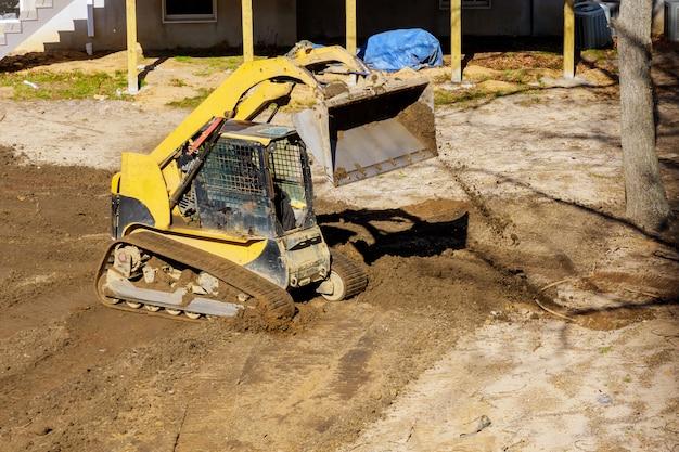 Mini-bulldozer mit schmutz, der landschaftsbauarbeiten ausführt