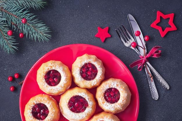Mini-bundt-ringkuchen mit roter heidelbeermarmelade auf dunkelheit mit tannenzweigen und beeren