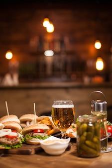 Mini-burger mit einem großen glas goldenem bier neben einem glas gurken. vintage-restaurant.