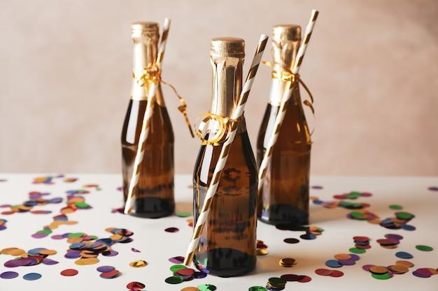 Mini-champagnerflaschen mit strohhalmen auf dekoriertem raum, nahaufnahme