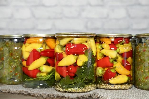 Mini-chilischoten in roten, gelben und orangen farben, in gläsern mit kräutern in dosen auf einem holztisch. hausgemachte eingelegte paprika nach asiatischer art. vorbereitungen für den winter. platz kopieren
