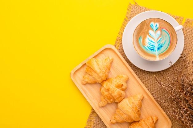 Mini-croissant der draufsicht in der holzschale und im kaffee. lebensmittelkonzept