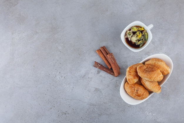Mini-croissants aus blätterteig mit goldener kruste und einer tasse tee.