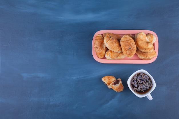 Mini-croissants aus blätterteig mit goldener kruste und einer tasse tee. Kostenlose Fotos