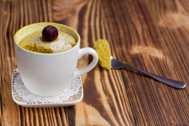 Mini cupcake in einer tasse mit einer kirsche oben drauf.