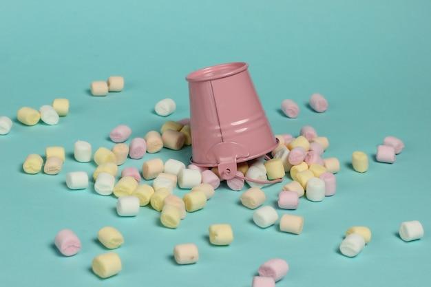 Mini-eimer mit vielen marshmallows auf blauem pastellhintergrund. minimalismus. süßigkeiten