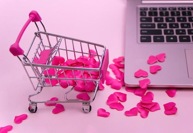 Mini-einkaufskorb mit roten herzen auf rosa hintergrund herzen sind über die tastatur verstreut