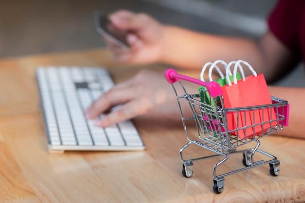 Mini-einkaufswagen, frau, die kreditkarte unter verwendung des laptops und des smartphone für das on-line-einkaufen hält