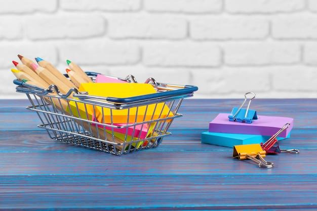 Mini-einkaufswagen mit bunten stiften und bleistiften