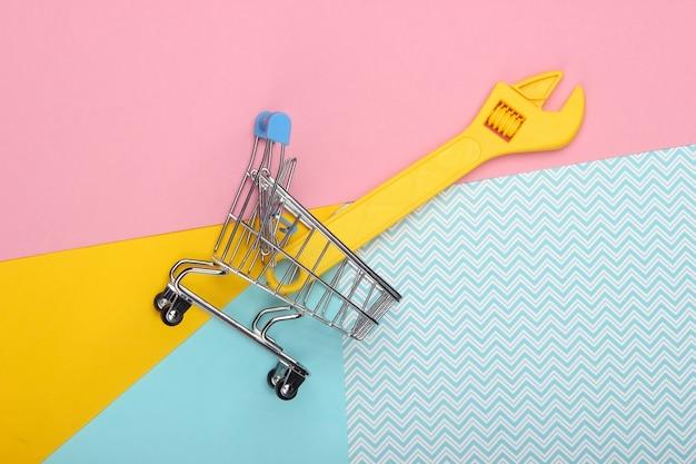 Mini-einkaufswagen mit einem spielzeugschlüssel auf einem farbigen pastellhintergrund. draufsicht. minimalismus