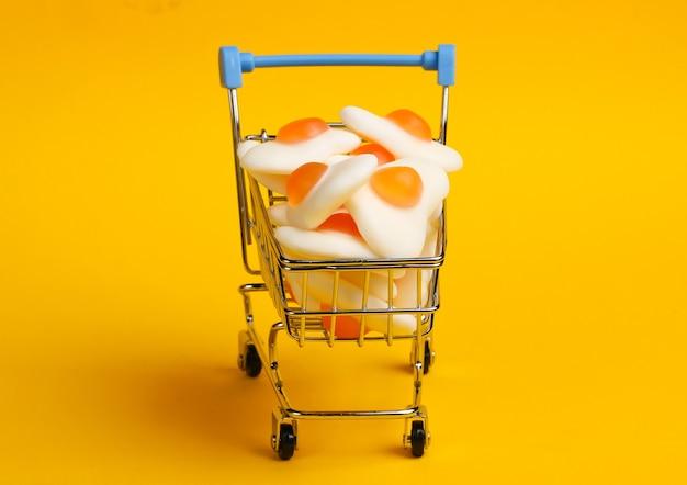 Mini-einkaufswagen mit marmeladen-spiegeleiern auf gelbem grund. süßigkeiten einkaufen, pastellfarbentrend, lebensmittelkonzept