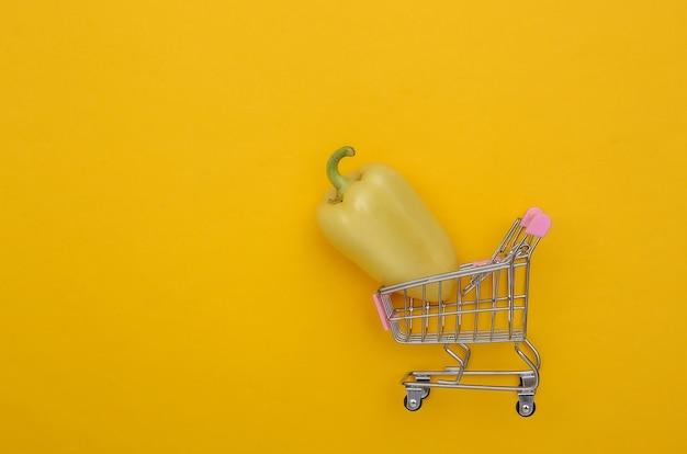 Mini-einkaufswagen mit paprika auf gelbem hintergrund. ansicht von oben