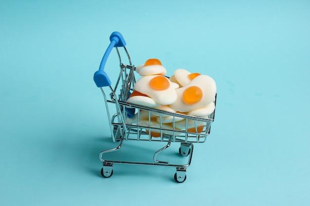 Mini-einkaufswagen mit spiegeleiern der marmelade auf blauem hintergrund. süßigkeiten einkaufen, pastellfarbentrend, lebensmittelkonzept