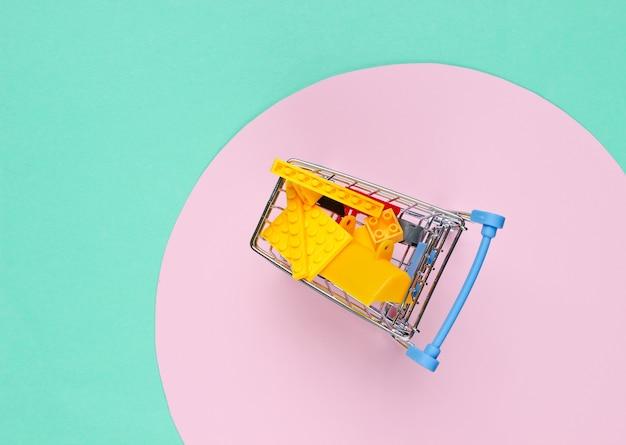 Mini-einkaufswagen mit spielzeugsteinen auf blau mit rosa pastellkreis