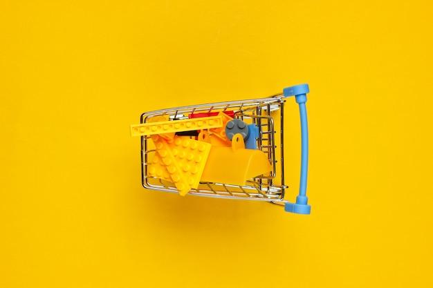 Mini-einkaufswagen mit spielzeugsteinen auf gelb