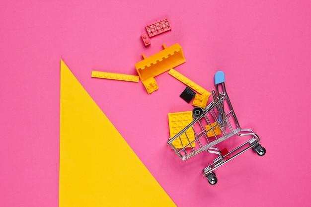Mini-einkaufswagen mit spielzeugsteinen auf gelbem rosa