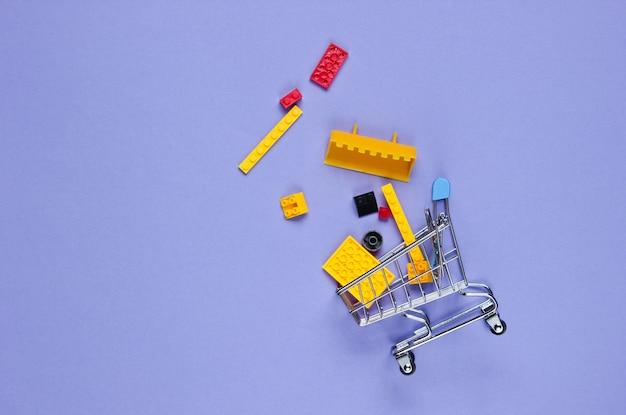 Mini-einkaufswagen mit spielzeugsteinen auf lila