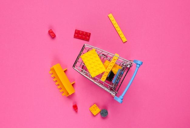 Mini-einkaufswagen mit spielzeugsteinen auf rosa