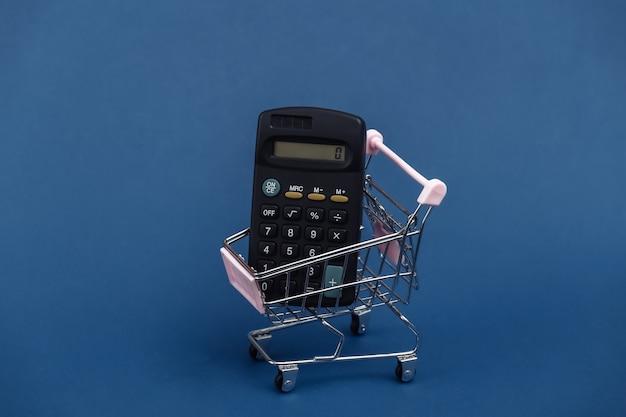 Mini-einkaufswagen mit taschenrechner auf klassischem blauem hintergrund