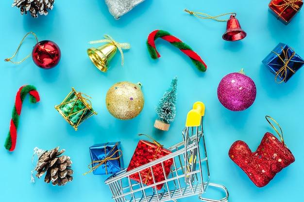 Mini-einkaufswagen mit weihnachtsschmuck auf blauem hintergrund für weihnachten und feiertage c