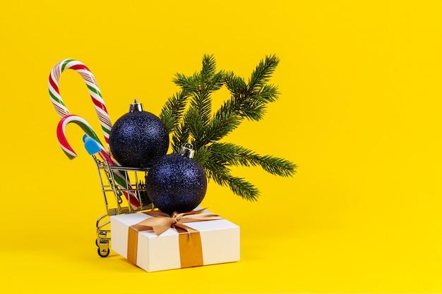Mini-einkaufswagen mit weihnachtsschmuck, tannenzweig, geschenkbox auf gelb