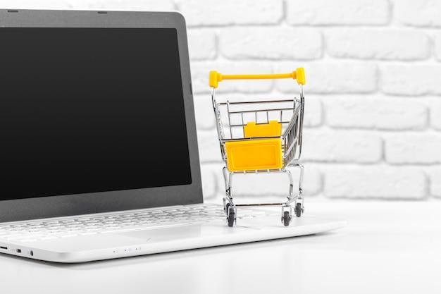 Mini einkaufswagen und laptop