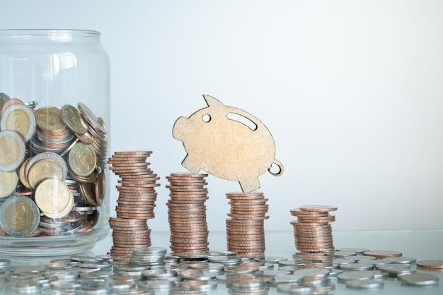 Mini figur sparschwein klettern auf stapel von münzen mit münzen im glas. geschäfts- und sparkonzept.