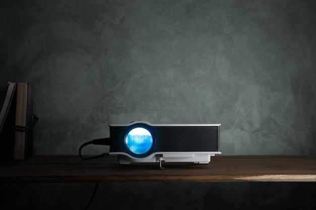 Mini führte projektor auf hölzerner tabelle in einem raumprojektorheimkinokonzept.