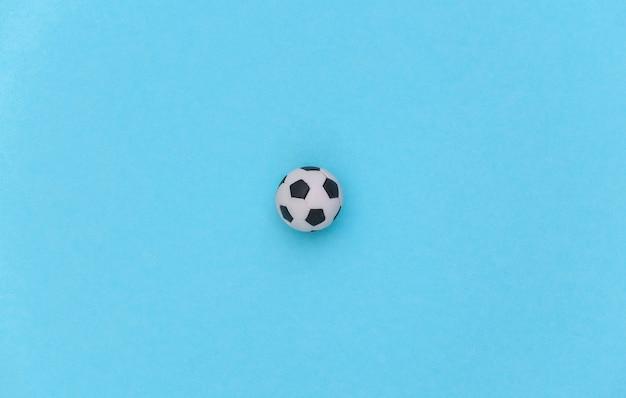 Mini-fußball auf blauem pastellhintergrund. minimalismus sportkonzept. ansicht von oben. flach legen