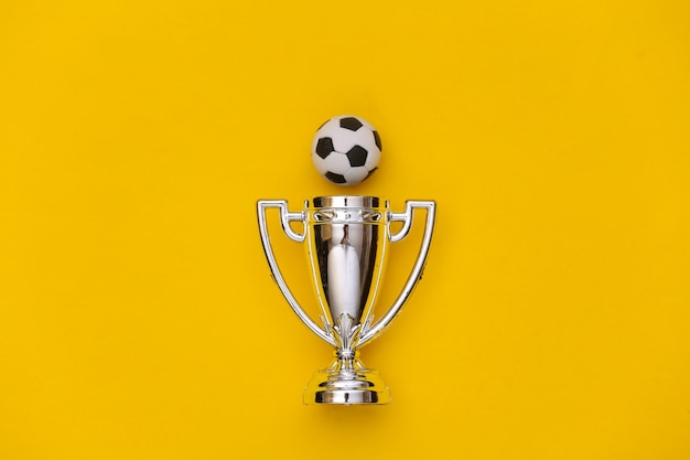Mini-fußball und meisterpokal auf gelbem hintergrund. minimalismus sportkonzept. ansicht von oben. flach legen