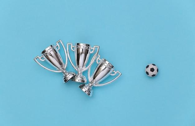 Mini-fußball und meisterschaftsbecher auf blauem hintergrund. minimalismus sportkonzept. ansicht von oben. flach legen