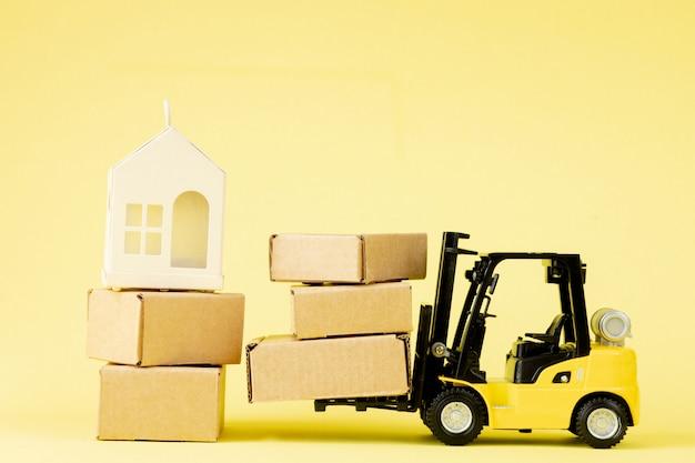 Mini-gabelstapler laden pappkartons. ideen für logistik- und transportmanagement und geschäftskonzept für das industriegeschäft.