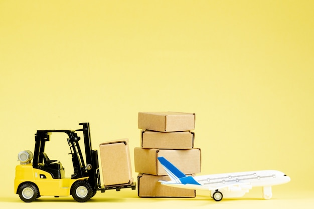 Mini-gabelstapler laden pappkartons im flugzeug. schnelle lieferung von waren und produkten.