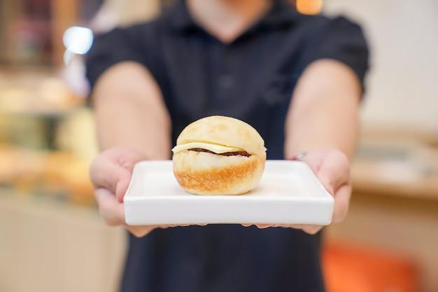 Mini-hamburger auf weißer quadratischer keramikschale mit handhaltung.