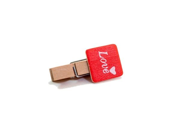 Mini holzwäscheklammer mit liebeswort auf weißem backgorund. valentinstag konzept.
