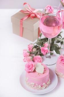 Mini kleiner kuchen mit rosa glasur, schönen rosen, tasse kaffee, geschenkbox auf dem weißen tisch.
