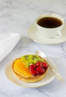 Mini-kuchen oder torte mit pudding und verschiedenen früchten in gelee.