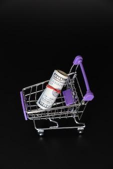 Mini-lebensmittelkorb mit 100 dollar auf schwarzem hintergrund. geld anlegen und aufbewahren. das konzept der sparsamkeit und der finanziellen bildung.
