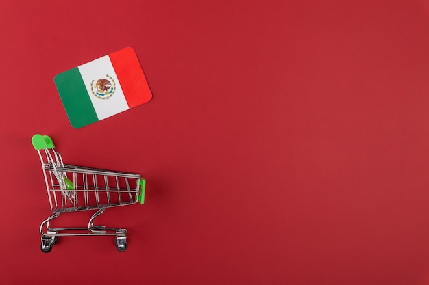 Mini leerer supermarkt-einkaufs-einkaufswagen, mexiko-flagge auf rotem hintergrund, konzeptverbrauch, import und export, kopierraum für text, horizontal, flach gelegt