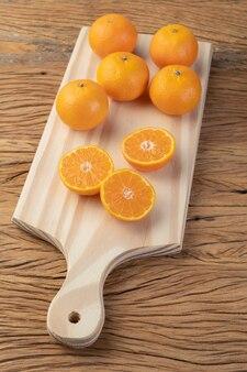 Mini-mandarinen auf einem brett über holztisch.