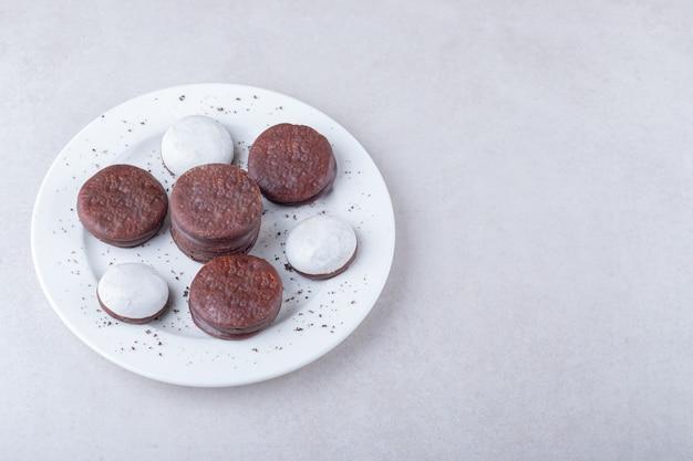 Mini-mousse-gebäck und schokoladenüberzogenes keksdessert auf einem teller auf der dunklen oberfläche