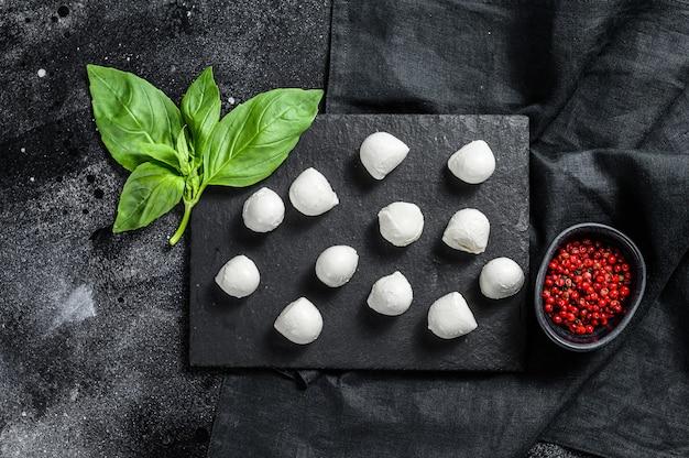 Mini-mozzarella-käsebällchen auf einem steinbrett mit basilikumblättern und rosa pfeffer