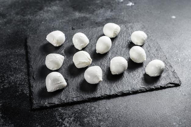 Mini mozzarella käsebällchen auf einem steinbrett. schwarzer hintergrund. draufsicht