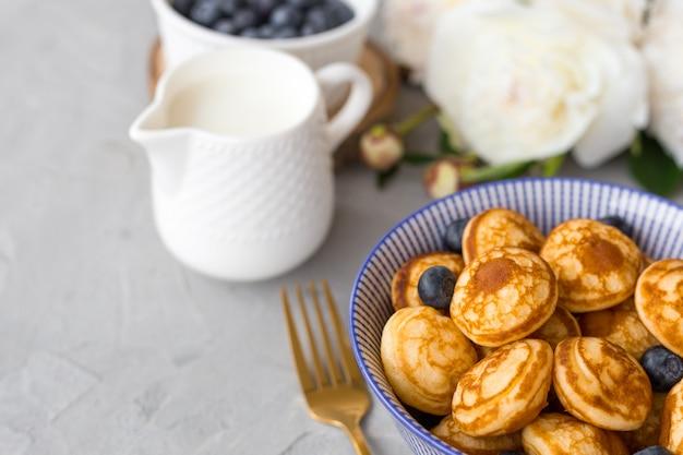 Mini-müsli-pfannkuchen mit blaubeeren in einer schüssel auf grauer oberfläche