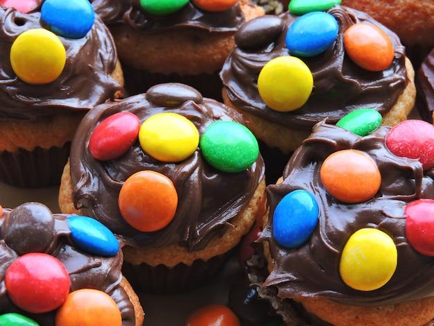 Mini-muffins mit belag aus schokoladencreme und farbigen süßigkeiten.