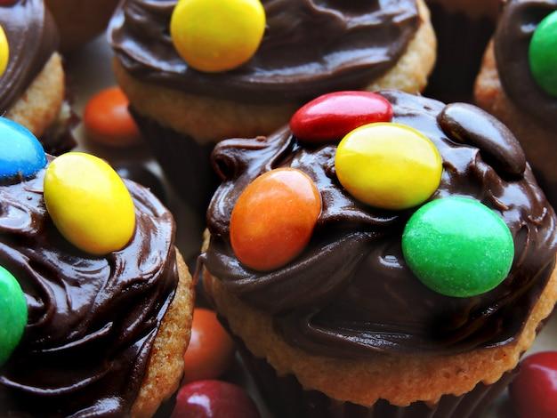 Mini-muffins mit schokoladencreme und bunten süßigkeiten.