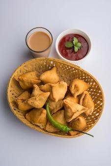 Mini oder kleine samosa mit sauce und heißem tee